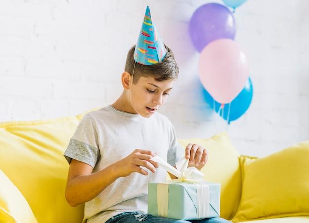 Ragazzo che si siede sul regalo di compleanno di unwrapping del sofà Foto Gratuite