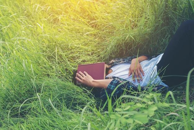 Ragazzo che si trova sull'erba con un libro sulla faccia Foto Gratuite