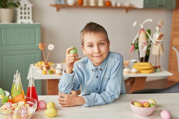 Ragazzo che tiene l'uovo di pasqua alla cucina Foto Premium