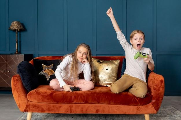 Ragazzo che vince giocando ai videogiochi con sua sorella Foto Gratuite