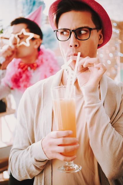 Ragazzo con gli occhiali con un cocktail a una festa gay. Foto Premium