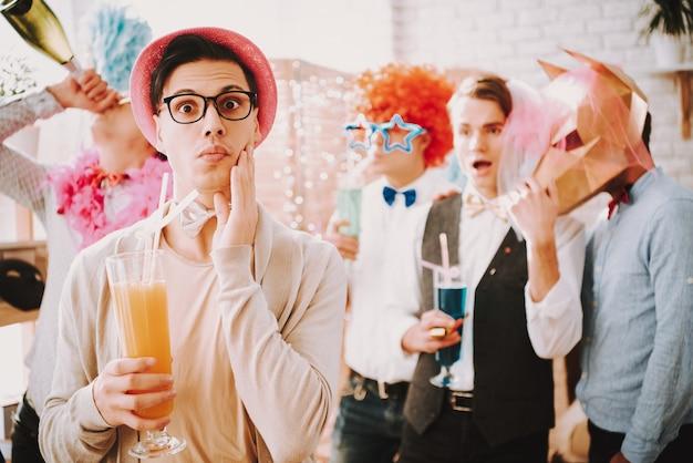 Ragazzo con gli occhiali con un cocktail a una festa gay Foto Premium