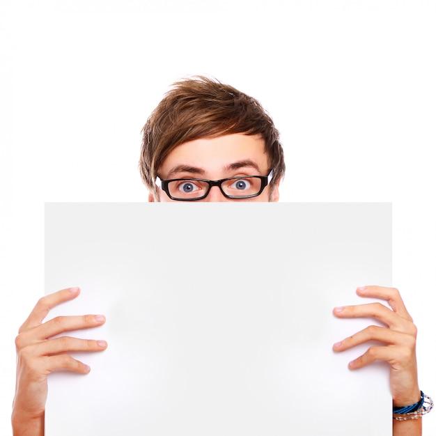 Ragazzo con gli occhiali tenendo a bordo bianco Foto Gratuite