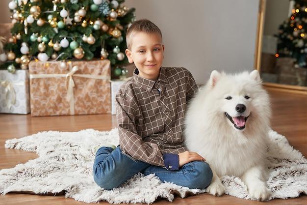 Ragazzo con il cane vicino all'albero di natale su natale Foto Premium