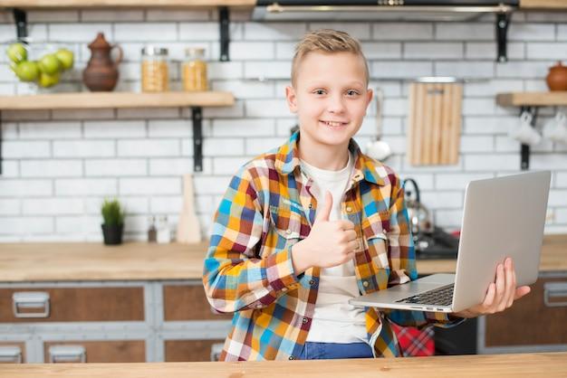 Ragazzo con il portatile in cucina Foto Gratuite