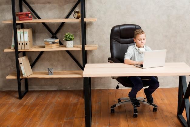 Ragazzo con il portatile in ufficio Foto Gratuite