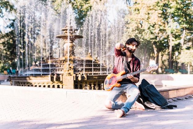 Ragazzo con la chitarra elettrica sulla fontana Foto Gratuite