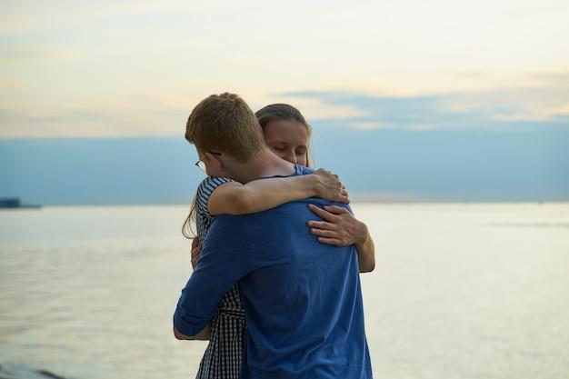 Ragazzo d'abbraccio della ragazza sulla spiaggia, amore teenager al tramonto Foto Premium