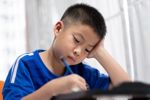 Ragazzo dei bambini che fa i compiti, bambino che scrive carta, concetto familiare, tempo di apprendimento, studente, ritorno a scuola Foto Premium