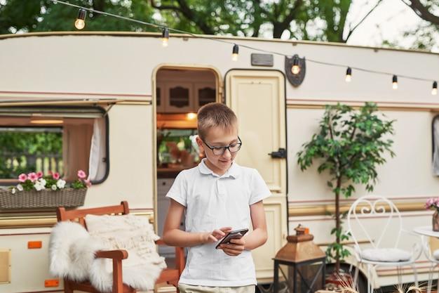 Ragazzo del bambino con un telefono in vacanza in estate vicino alla casa su ruote Foto Premium