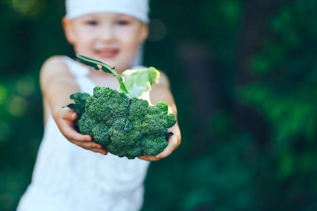 Ragazzo del coltivatore in camici bianchi e fascia per capelli grigia che mostra i broccoli organici freschi in giardino Foto Premium