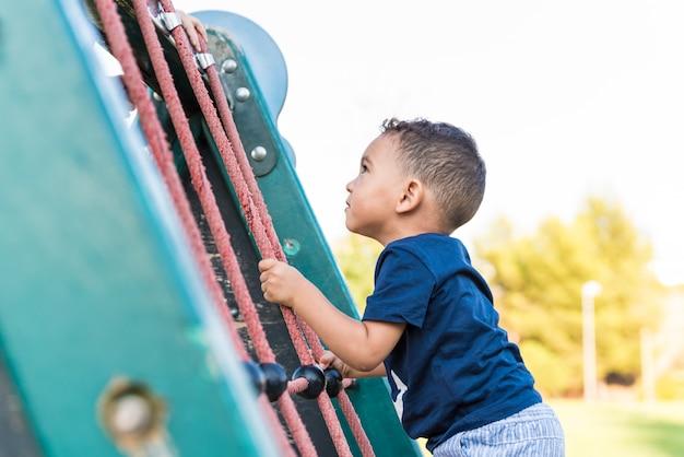 Ragazzo del piccolo bambino che scala una corda nel parco. Foto Premium