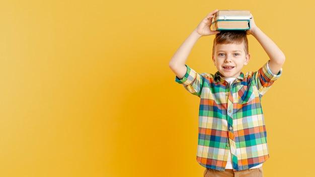 Ragazzo dello copia-spazio con i libri sulla sua testa Foto Gratuite