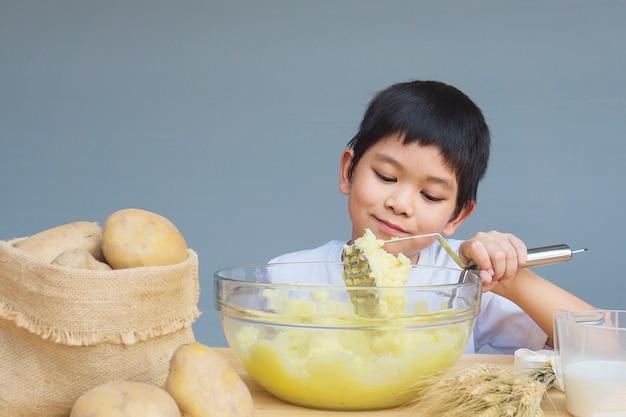 Ragazzo di 7 anni che fa felicemente purè di patate Foto Gratuite