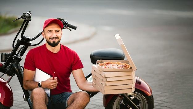 Ragazzo di consegna di tiro medio seduto sulla moto Foto Gratuite