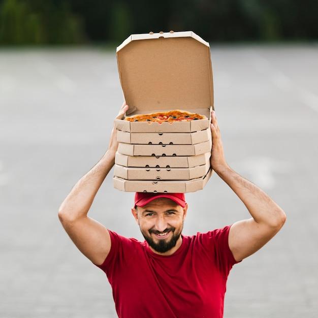 Ragazzo di consegna vista frontale con scatole per pizza in testa Foto Gratuite