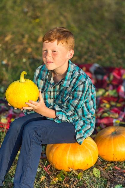 Ragazzo di redhead che si siede su una zucca gialla Foto Gratuite