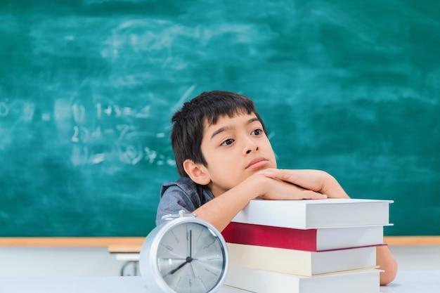 Ragazzo di scuola asiatico che pensa e che sogna con il libro e la sveglia sulla tavola Foto Premium