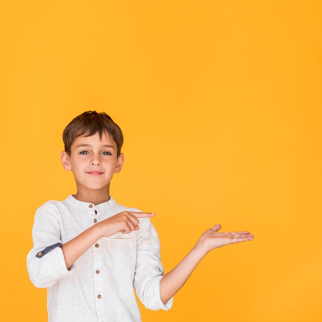 Ragazzo di smiley che indica in una direzione con lo spazio della copia Foto Gratuite