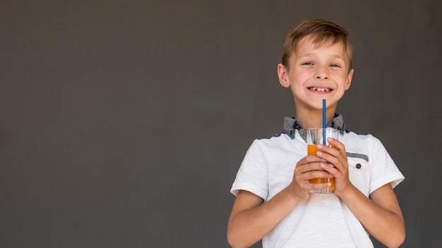 Ragazzo di smiley che tiene un succo d'arancia con lo spazio della copia Foto Gratuite