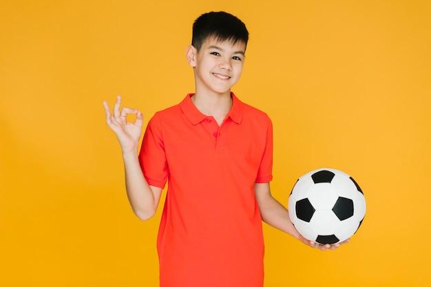 Ragazzo di smiley che tiene una sfera di calcio Foto Gratuite