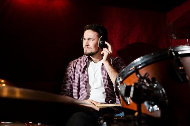Ragazzo di vista frontale suonare la batteria e fare facce buffe Foto Gratuite