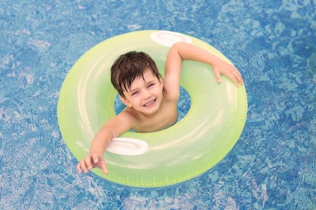 Ragazzo di vista superiore in piscina con galleggiante Foto Gratuite