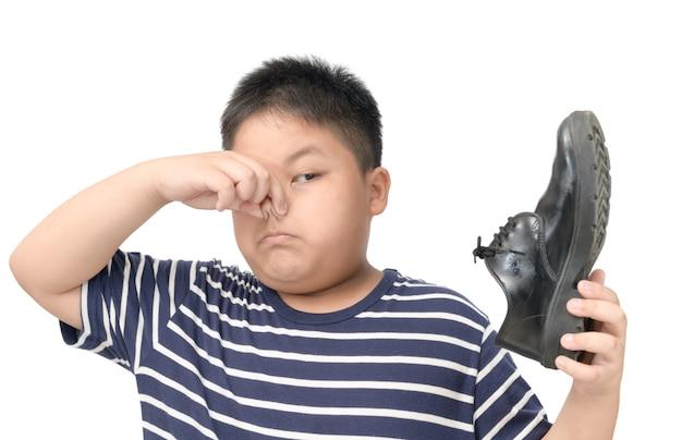 Ragazzo disgustato in possesso di un paio di scarpe in pelle puzzolente Foto Premium