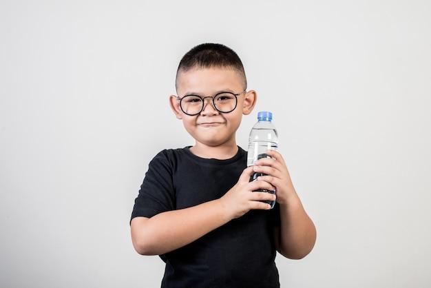 Ragazzo divertente con la bottiglia di acqua nel colpo dello studio Foto Gratuite