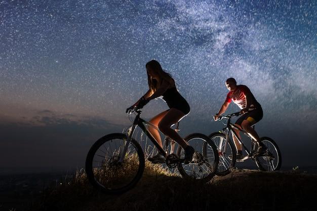 Ragazzo e ragazza in sella a una bicicletta sulla collina di notte Foto Premium