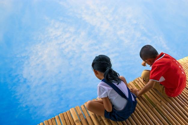 Ragazzo e ragazza sul concetto di ponte e cielo, scoperta e avventura di bambù. Foto Premium