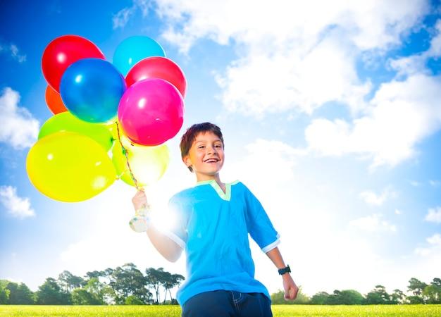 Ragazzo felice all'aperto con una dozzina di palloni di elio. Foto Premium