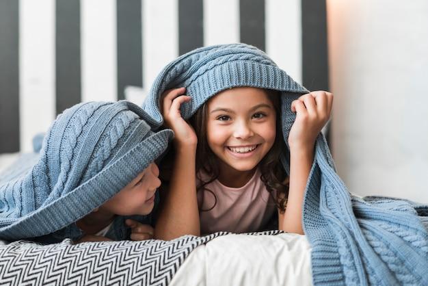 Ragazzo felice che esamina sua sorella che si trova sotto la coperta sul letto Foto Gratuite