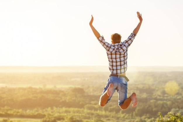 Ragazzo felice che salta in cima sullo sfondo Foto Premium