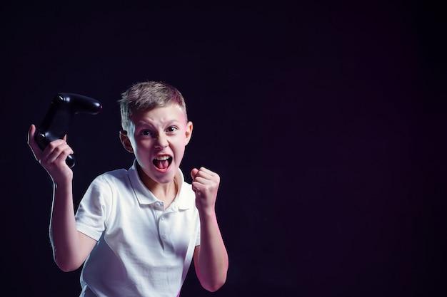 Ragazzo felice con la bocca aperta e il joystick che grida di gioia dopo aver vinto nel videogioco sulla parete nera Foto Premium