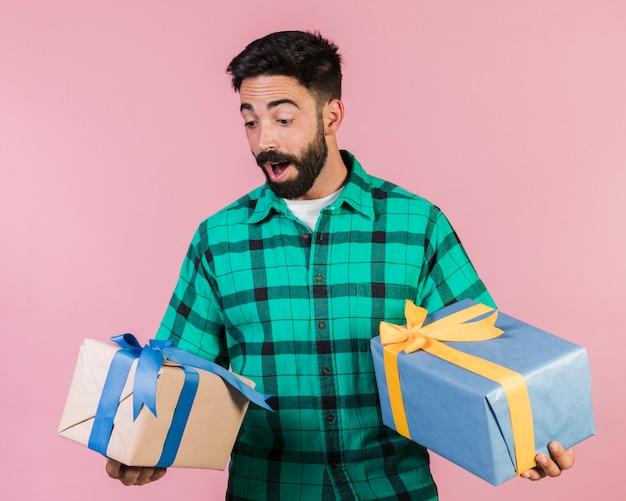 Ragazzo felice del colpo del tipo che tiene i regali Foto Gratuite