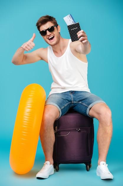 Ragazzo felice in occhiali da sole seduto su una borsa Foto Gratuite
