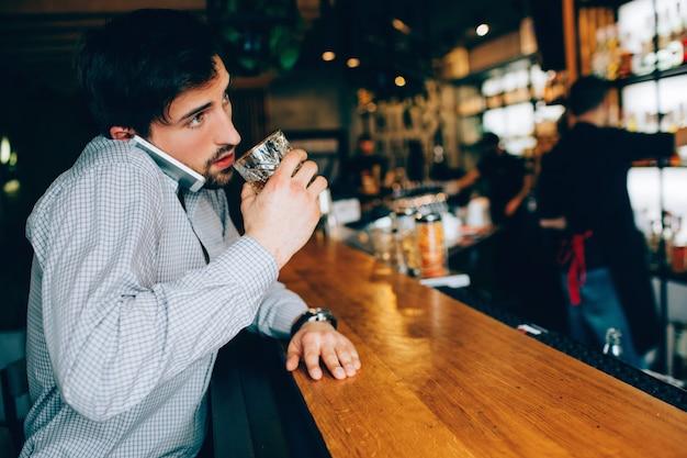 Ragazzo giovane e moro seduto allo stand del cameriere nel locale e bevendo un po 'di alcol. inoltre parla al telefono e cerca di bere allo stesso tempo. barman è lontano da lui. Foto Premium