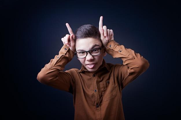 Ragazzo, il ragazzo fa una smorfia su uno sfondo nero Foto Premium
