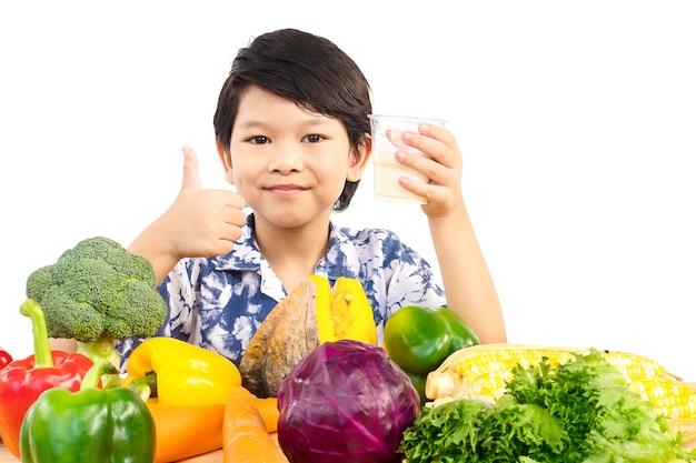 Ragazzo in buona salute asiatico che mostra espressione felice con un bicchiere di latte e varietà di verdure fresche Foto Gratuite