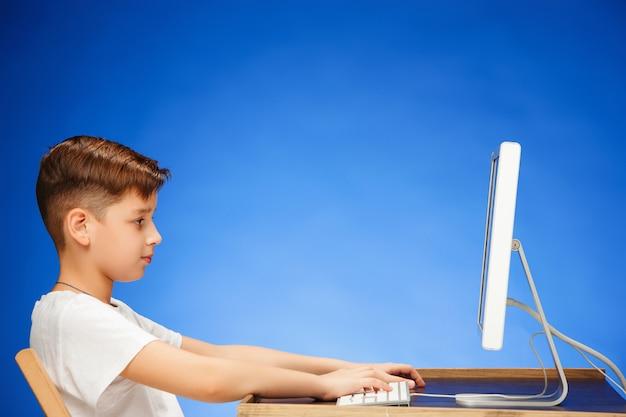 Ragazzo in età scolare che si siede davanti al computer portatile del monitor Foto Gratuite