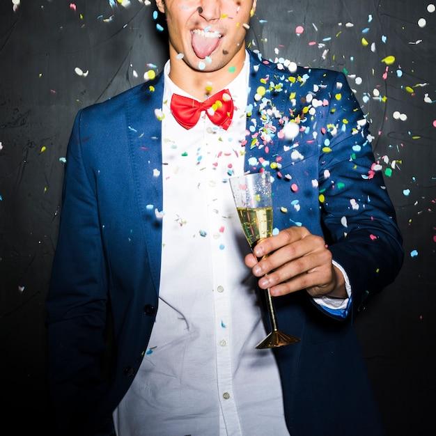 Ragazzo in giacca da sera con il bicchiere tra il lancio di coriandoli Foto Gratuite