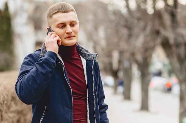 Ragazzo in giacca semplice sta con telefono Foto Premium