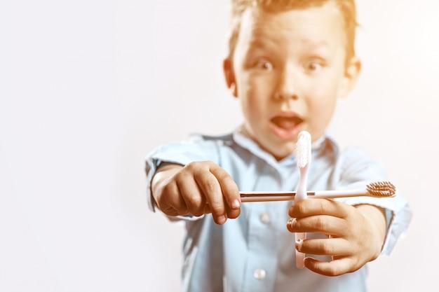 Ragazzo in una camicia blu che tiene spazzolini da denti e gioisce Foto Premium