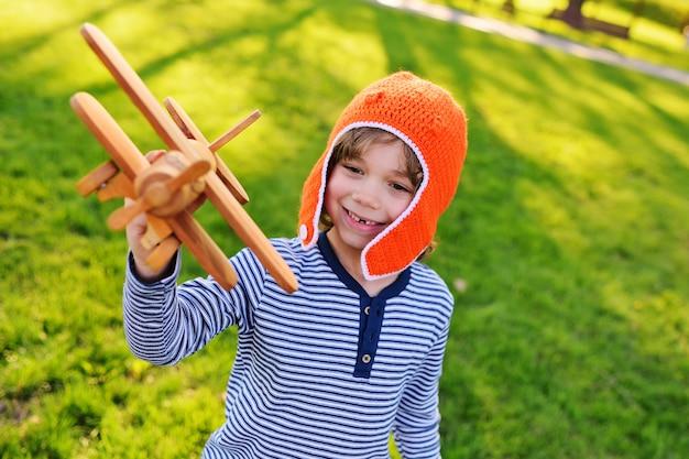 Ragazzo nel pilota arancio del casco che gioca in aereo di legno del giocattolo contro il fondo dell'erba Foto Premium