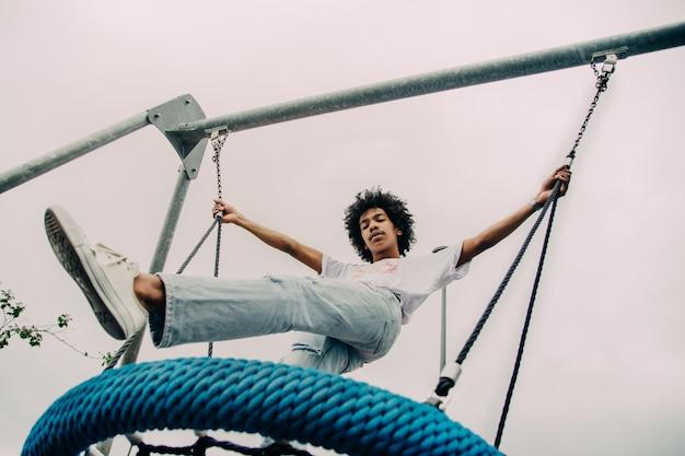 Ragazzo nero in piedi su un grande swing Foto Gratuite