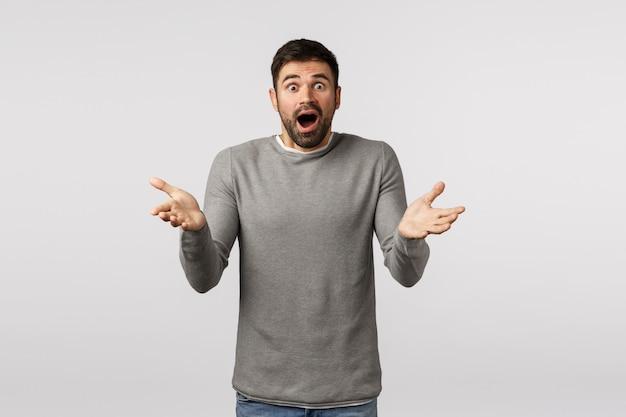 Ragazzo nervoso scioccato e preoccupato lasciato solo con il bambino, sentendosi confuso non so cosa fare, alza le mani come se afferrasse qualcosa di fragile che cade, ansimando ansiosamente, apri la bocca e guarda la telecamera Foto Premium