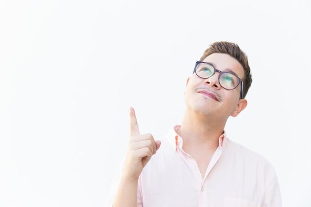 Ragazzo pensieroso positivo in occhiali che indica dito su Foto Gratuite