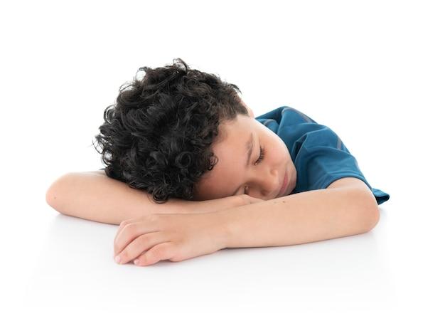 Ragazzo pigro esaurito piccoli giovani addormentato sulla tabella bianca su fondo bianco Foto Premium