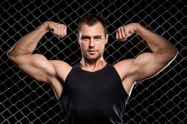 Ragazzo potente che mostra i suoi muscoli sul recinto Foto Gratuite